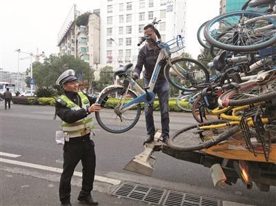 市公安局交警支队对辖区内的僵尸车、废弃共享单车等进行搬运处理